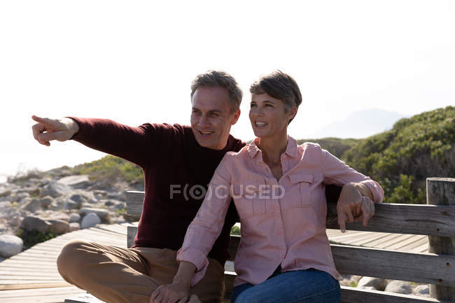 Front view of an adult Caucasian couple enjoying free time sitting on a bench and smiling on a sunny day — Foto stock