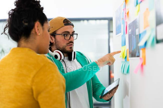 Бічний погляд на молодого кавказького чоловіка і змішаної расової жінки, які працюють у творчому кабінеті, стоять біля дошки, обговорюють. — стокове фото
