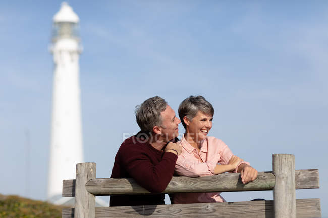 Front view of an adult Caucasian couple enjoying free time sitting on a bench and smiling near a lighthouse on a sunny day — Foto stock