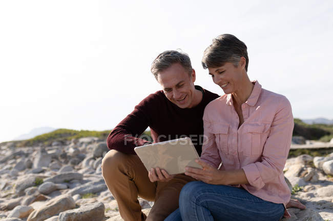 Front view of an adult Caucasian couple enjoying free time relaxing together on a beach using a tablet on a sunny day — Foto stock