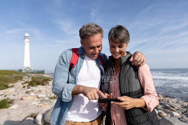 Vista frontale di una coppia caucasica adulta che si gode il tempo libero usando uno smartphone e sorridendo vicino a un faro vicino al mare in una giornata di sole — Foto stock