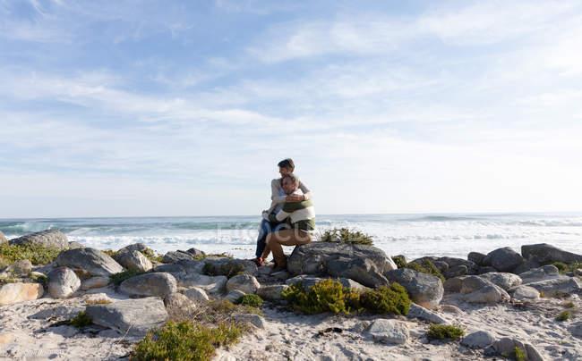 Вид спереди на взрослую кавказскую пару, наслаждающуюся свободным временем, обнимающуюся на пляже у моря в солнечный день — стоковое фото
