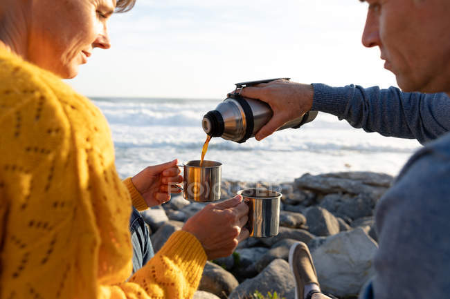 Front view close up of an adult Caucasian couple enjoying free time relaxing together on a beach beside the sea drinking coffee on a sunny day — Foto stock
