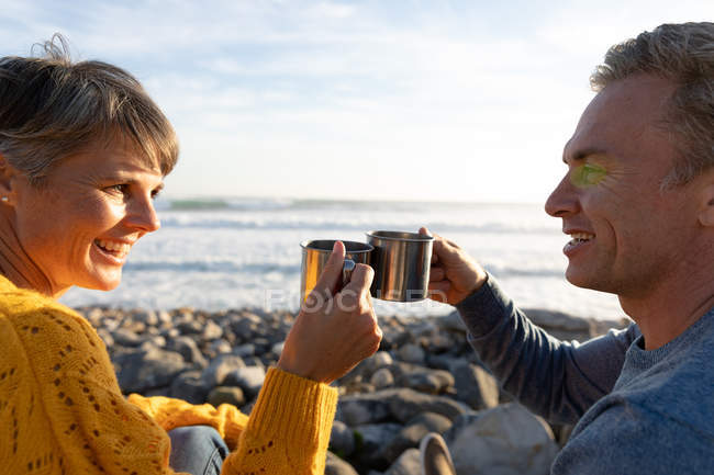 Front view close up of an adult Caucasian couple enjoying free time relaxing together on a beach beside the sea drinking coffee on a sunny day — Stock Photo