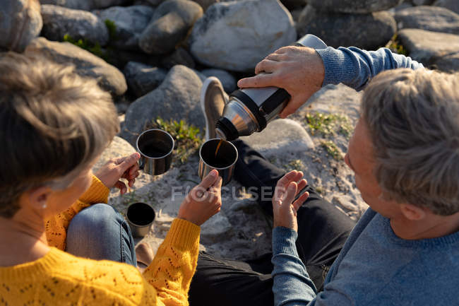 Overhead view close up of an adult Caucasian couple enjoying free time relaxing together drinking coffee on a sunny day — Foto stock