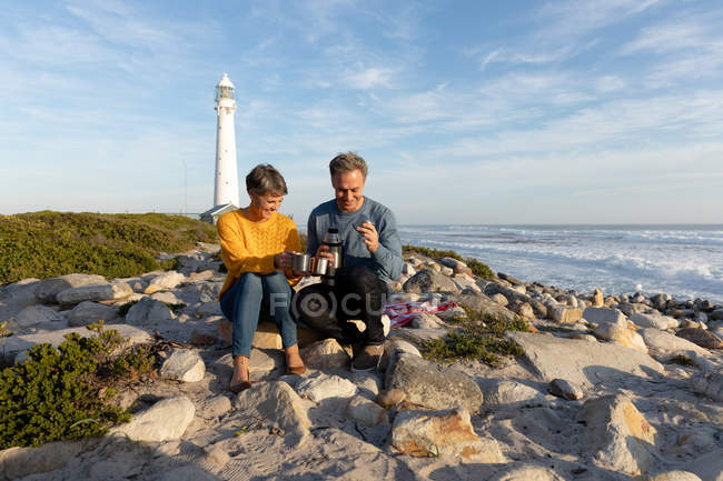 Front view of an adult Caucasian couple enjoying free time relaxing together on a beach beside the sea drinking coffee near a lighthouse on a sunny day — Foto stock