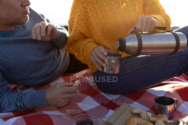 Front view close up of an adult Caucasian couple enjoying free time relaxing together on a beach drinking coffee on a sunny day — Foto stock