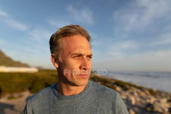 Vista frontal close-up de um homem caucasiano desfrutando de tempo livre em uma praia com vista para o mar em um dia ensolarado — Fotografia de Stock