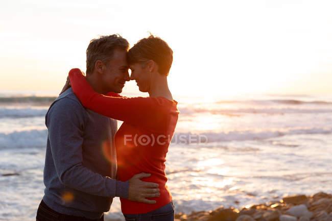Вид сбоку на взрослую кавказскую пару, наслаждающуюся свободным временем, отдыхающую вместе на пляже, обнимающемся рядом с морем в солнечный день — стоковое фото