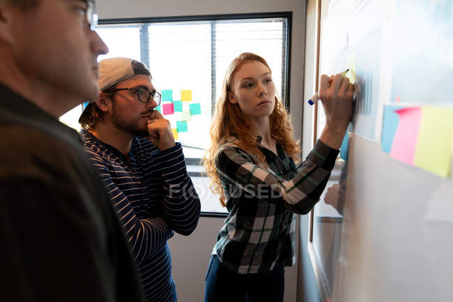 Front view of a young Caucasian woman working in a creative office, writing on a whiteboard with her male Caucasian colleagues looking on. — Stock Photo