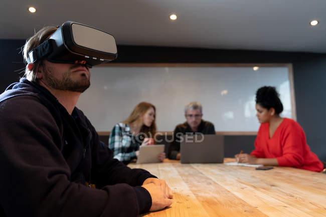 Seitenansicht eines jungen kaukasischen Mannes, der an einem Tisch in einem Konferenzraum für kreative Büros sitzt und bei einem Treffen im Hintergrund ein Vr-Headset mit seinen Kollegen trägt. — Stockfoto