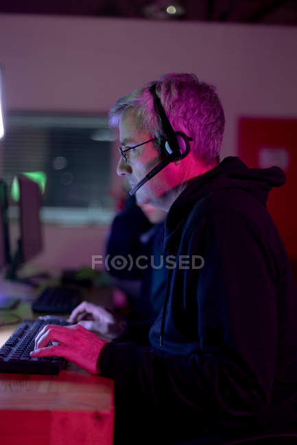 Side view of a caucasian gamer man working in a creative office, wearing reading glasses and headset looking at computer screen — Stock Photo