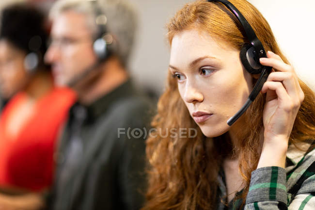 Side view of a young Caucasian woman in a creative office, wearing headset with her colleagues in the background. This is a new start up business venture — Stock Photo