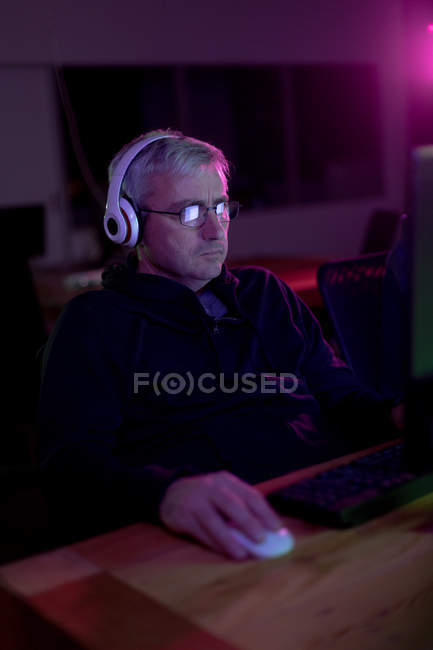 Front view of a Caucasian man working in a creative office, wearing reading glasses, listening to music with headphones on, looking at computer screen — Stock Photo