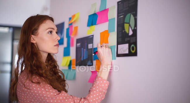 Side view of a young Caucasian woman working in a creative office standing by a whiteboard writing on memo notes — Stock Photo
