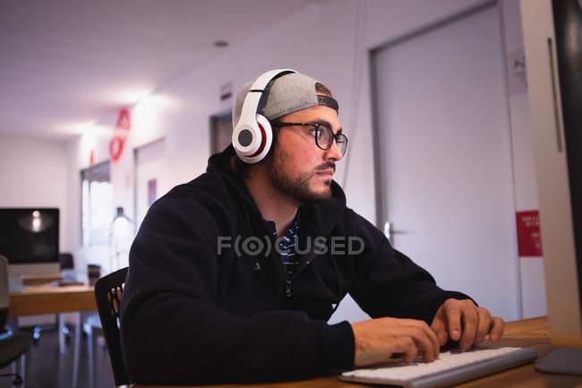 Vista laterale di un giovane caucasico che lavora in un ufficio creativo, seduto alla scrivania usando un computer, digitando e ascoltando musica con le cuffie, indossando occhiali e un cappello — Foto stock