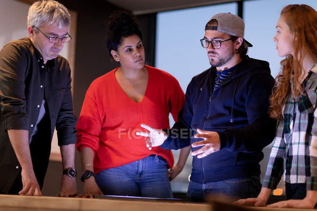 Vista frontal de un grupo diverso de creativos de pie junto a una mesa en una sala de conferencias de oficina, en una discusión en una reunión . - foto de stock
