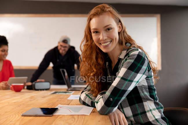 Retrato de uma jovem branca sentada em uma mesa em uma sala de conferências criativa, sorrindo para a câmera com seus colegas em uma reunião em segundo plano. — Fotografia de Stock