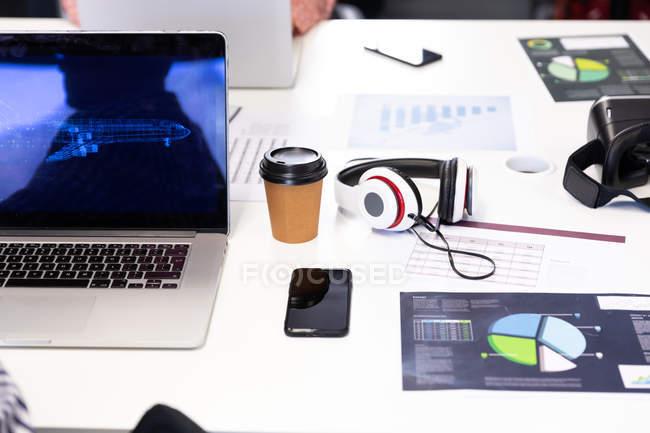 Vista ad alto angolo di una scrivania in un ufficio creativo con computer portatile, smartphone, cuffie e tazzina da caffè . — Foto stock