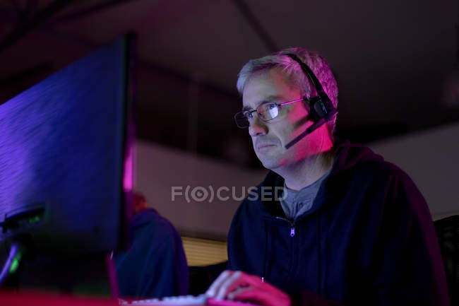 Side view of a Caucasian man working in a creative office, wearing reading glasses and headset looking at computer screen — Stock Photo