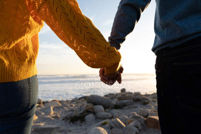 Mid section of couple enjoying free time on a beach holding hands beside the sea on a sunny day — Stock Photo