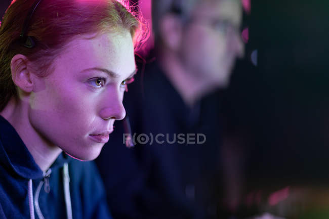 Side view of a young Caucasian woman gamer working in a creative office, her male colleague working in the background — Stock Photo