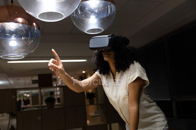 Front view of a young mixed race professional woman working late in a modern office using a VR headset and pointing upwards — Stock Photo