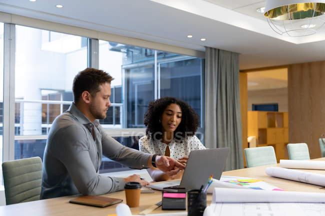 Vista lateral de un joven profesional caucásico y mujer de raza mixta que trabaja en una oficina moderna, sentado en un escritorio con ordenador portátil. - foto de stock