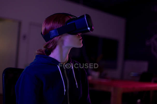 Side view of a young Caucasian female gamer working in a creative office, wearing vr headset this is a start up business — Stock Photo