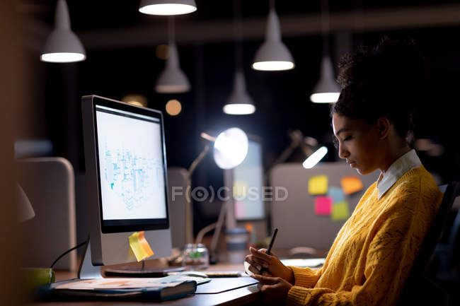 Side view of a young mixed race professional woman working late in a modern office, sitting at a desk in front of a computer monitor making notes — Stock Photo