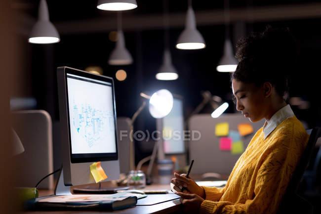 Vista laterale di una giovane donna professionista di razza mista che lavora fino a tardi in un ufficio moderno, seduta a una scrivania di fronte a un monitor del computer che prende appunti — Foto stock