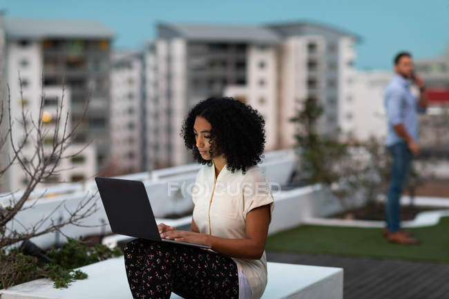 Front view of a young mixed race professional woman working late at a modern office, sitting on the roof terrace using a laptop computer, her male colleague standing in the background — Stock Photo