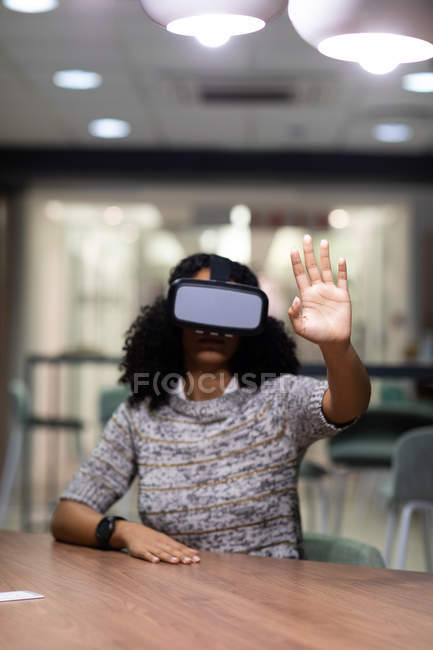 Front view of a young mixed race professional woman working late in a modern office, sitting at a desk wearing a VR headset, with one hand raised in front of her — Stock Photo