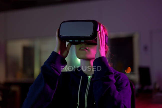 Front view of a young caucasian female gamer working in a creative office, wearing vr headset, this is a start up business — Stock Photo