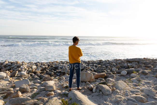 Vista trasera de una mujer caucásica disfrutando de tiempo libre en una playa junto al mar en un día soleado que está mirando hacia el océano - foto de stock