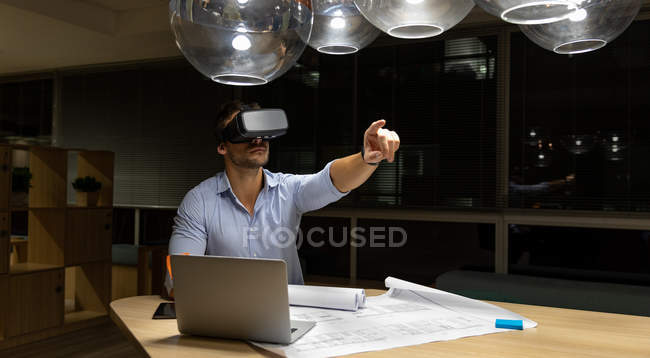 Frontansicht eines jungen kaukasischen Berufstätigen, der spät in einem modernen Büro arbeitet, am Schreibtisch sitzt, einen Laptop und ein Vr-Headset benutzt und in die Ferne zeigt — Stockfoto