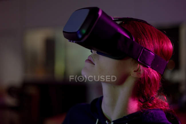 Side view of a young Caucasian woman working in a creative office, wearing VR headset. This is a start up business — Stock Photo