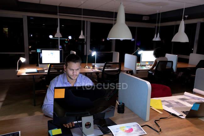 Передній погляд на молодого кавказького професіонала, який працював у сучасному офісі, сидячи за столом, використовуючи настільний комп