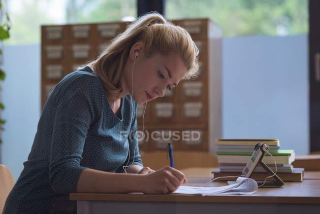 Étudiant universitaire effectuant une affectation en classe au collège — Photo de stock