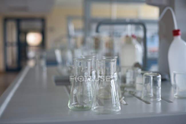 Primo piano dei becher sulla scrivania in laboratorio — Foto stock