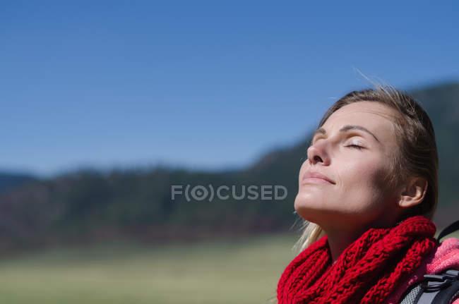 Gros plan de la femme les yeux fermés contre le ciel bleu — Photo de stock