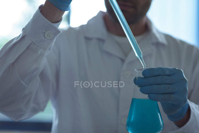 Mid-section of university student doing a chemical experiment in laboratory — Stock Photo