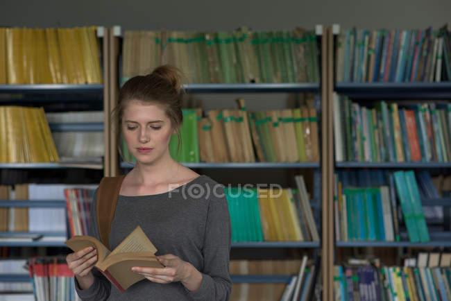 Jeune étudiante lisant un livre debout à la bibliothèque — Photo de stock