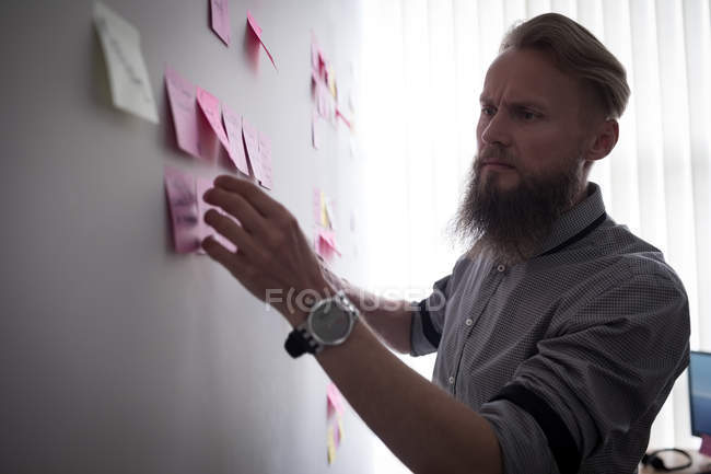 Attentive executive reading sticky notes in office — Stock Photo