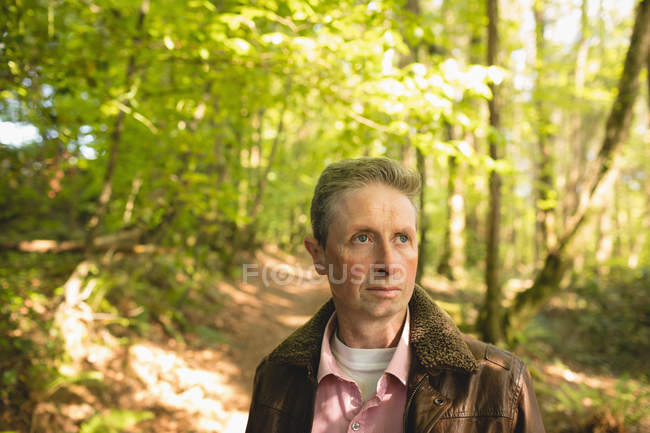 Духовний зрілий чоловік стоїть у лісі. — стокове фото