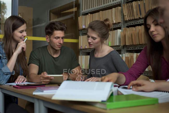 Estudiantes universitarios que estudian en el escritorio en las bibliotecas - foto de stock