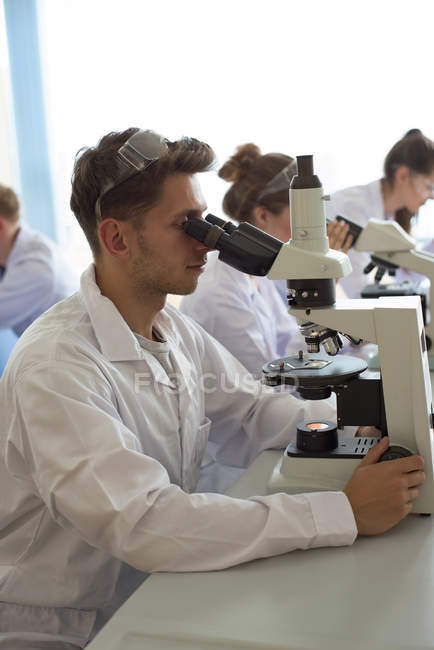 College students using microscope while practicing experiment in lab — Stock Photo