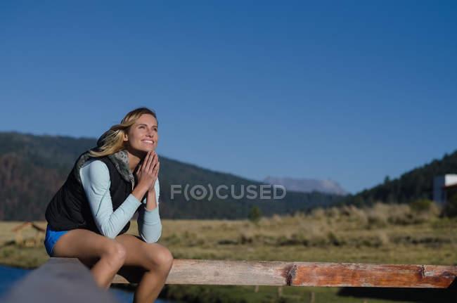 Улыбающаяся задумчивая женщина, сидящая на перилах против ясного голубого неба — стоковое фото