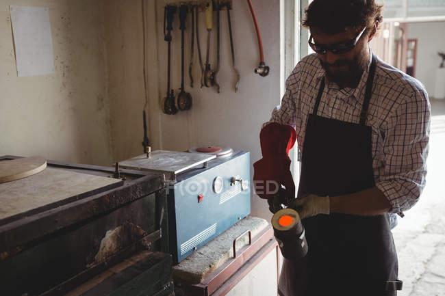 Ремесленник держит расплавленный металл в мастерской — стоковое фото