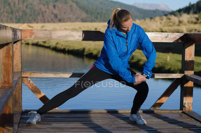 Young female athlete stretching while exercising on pier by lake — Stock Photo